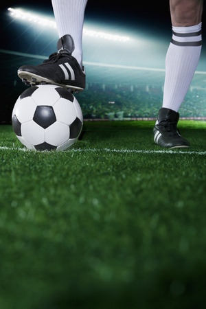 soccer sport: Close up of feet on top of soccer ball, night time in the stadium Stock Photo