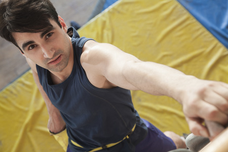directly above: Close-up of young man climbing up a climbing wall in an indoor climbing gym, directly above