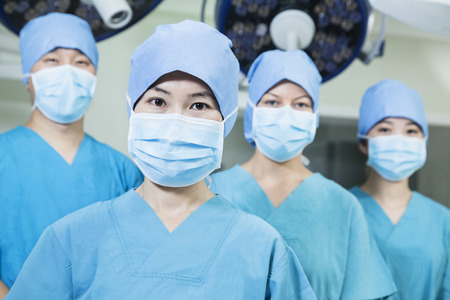 above 18: Team of surgeons wearing surgical masks in the operating room, looking at camera