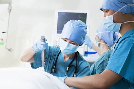 Two surgeons working at the operating table, holding surgical equipment photo