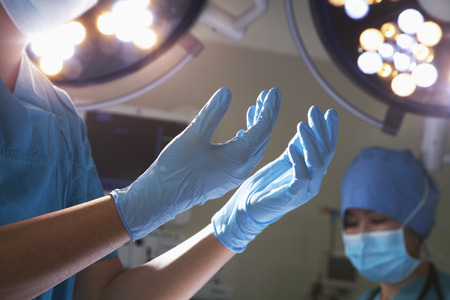midsection: Midsection view of hands in surgical gloves and surgical lights in the operating room