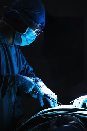 Surgeon looking down, working, and holding surgical equipment with patient lying on the operating table  photo