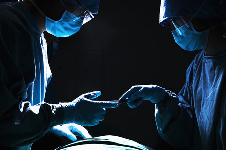 by pass surgery: Two surgeons working and passing surgical equipment in the operating room, dark