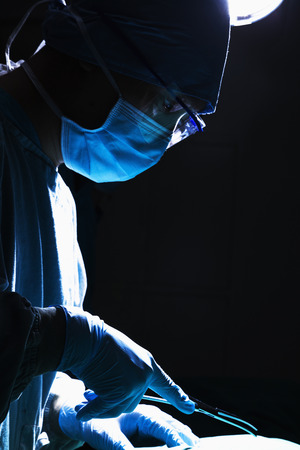 surgical equipment: Surgeon looking down, concentrating, and holding surgical equipment in the operating room
