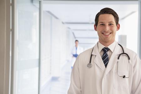 bata de laboratorio: Retrato de joven m�dico en bata de laboratorio en el hospital, mirando la c�mara