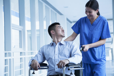 three day beard: Smiling female nurse pushing and assisting patient in a wheelchair in the hospital  Stock Photo