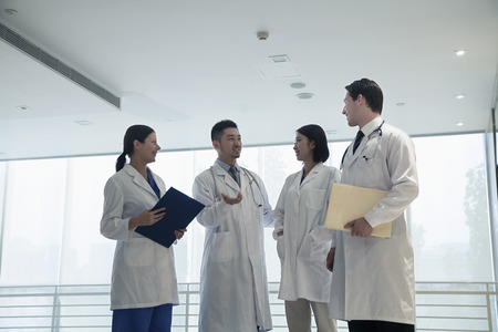 above 18: Four doctors standing, talking, and smiling in the hospital