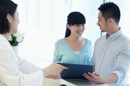 above 18: Doctor and smiling couple standing by the counter in the hospital looking at medical record Stock Photo