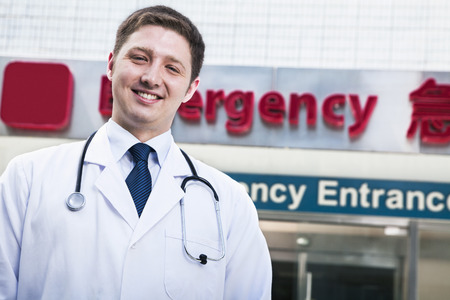 emergency room: Portrait of young smiling doctor outside of the hospital, emergency room sign in the background