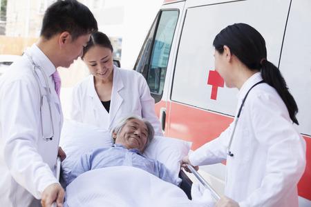 paciente en camilla: Tres m�dicos que ruedan en un paciente de edad avanzada en una camilla delante de una ambulancia