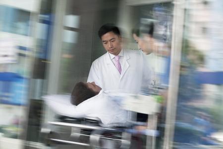 paciente en camilla: Dos m�dicos que ruedan en un paciente en una camilla a trav�s de las puertas del hospital Foto de archivo