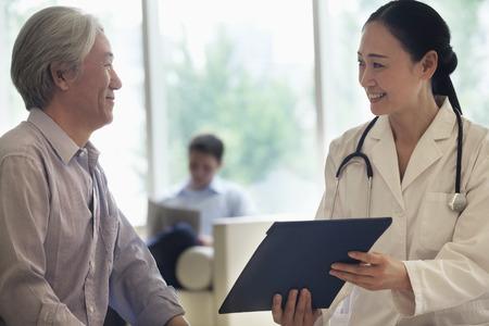 medico y paciente: Doctor y paciente femeninos sentarse y discutir la historia cl�nica en el hospital