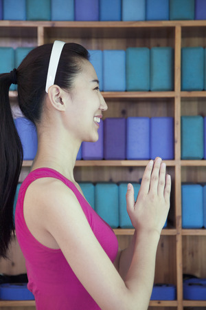 clasped: Portrait of young women doing yoga with hands clasped together, side view