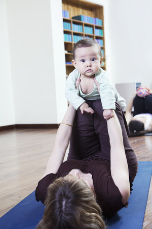 some under 18: Mother lying on back and holding her baby during a yoga class Stock Photo