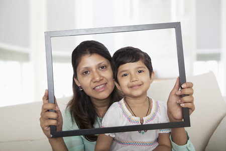 some under 18: Mother and daughter holding up a picture frame and looking through it