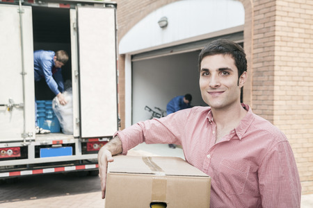 above 18: Smiling man holding a cardboard box and moving into his new home
