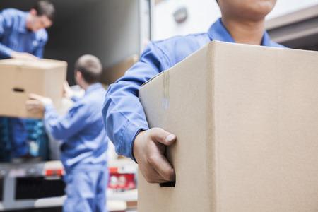 carga: Movers descarga de un cami�n de mudanzas Foto de archivo