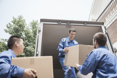 home moving: Movers unloading a moving van, passing a cardboard box
