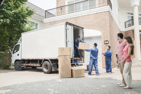 people moving: Young couple watching movers move boxes from the moving van Stock Photo