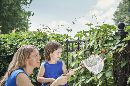 some under 18: Smiling mother and daughter holding a butterfly and attempting to catch a butterfly in the garden Stock Photo