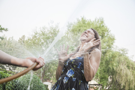 above 30: Couple playing with a garden hose and spraying each other outside in the garden, woman is trying to defend herself