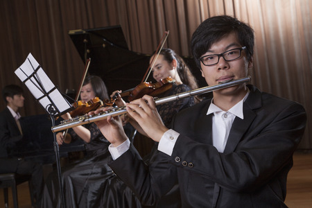 Flautist holding and playing the flute during a performance, looking at the camera Stock Photo