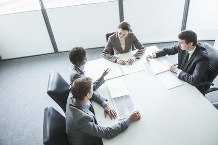the working day: Cuatro hombres de negocios sentados alrededor de una mesa y tener una reunión de negocios, vista de ángulo alto