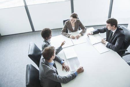 business confidence: Four business people sitting around a table and having a business meeting, high angle view