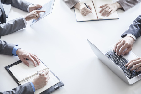 Four business people around a table and during a business meeting, hands only