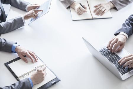 Vier mensen uit het bedrijfsleven rond een tafel en tijdens een zakelijke bijeenkomst, handen alleen