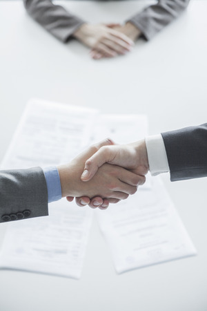 above 18: Two business people shaking hands over the table, hands only
