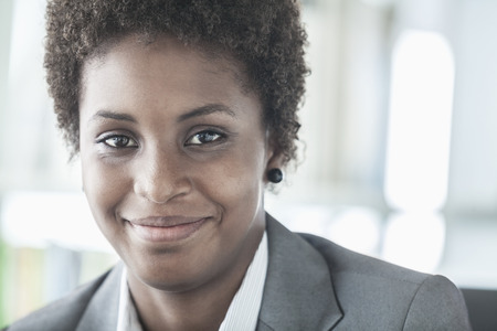 above 18: Portrait of smiling young businesswoman with short hair looking at the camera, head and shoulders