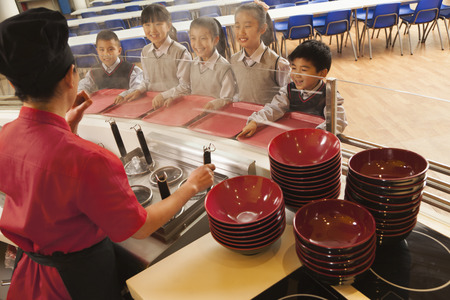 school cafeteria: School cafeteria worker serves noodles to students