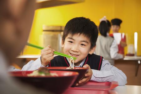 school cafeteria: School boy eats noodles in school cafeteria
