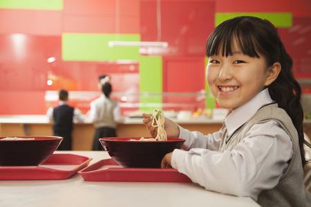school cafeteria: School girl eats noodles in school cafeteria
