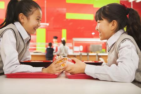 Two school girls talk over lunch in school cafeteria Foto de archivo