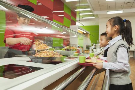 comedor escolar: Los escolares de pie en línea en la cafetería de la escuela Foto de archivo