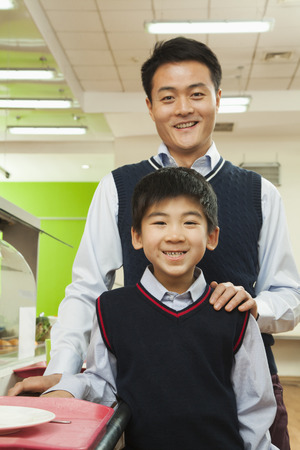 generation gap: Teacher and school boy portrait in school cafeteria