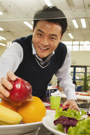 school cafeteria: Teacher reaching for healthy food in school cafeteria Stock Photo