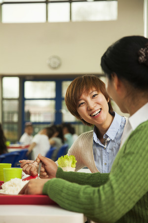 school cafeteria: Teachers talking at lunch in school cafeteria