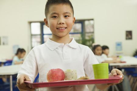 El muchacho de escuela que sostiene la bandeja de comida en la cafetería de la escuela Foto de archivo - 35992791