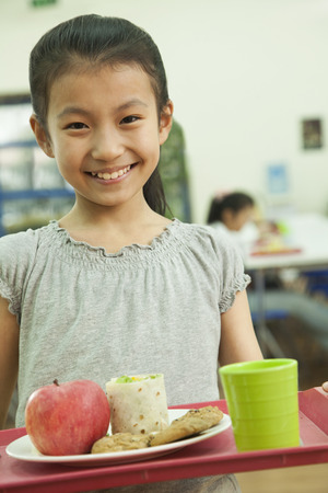 cafeteria tray: School girl holding food tray in school cafeteria Stock Photo