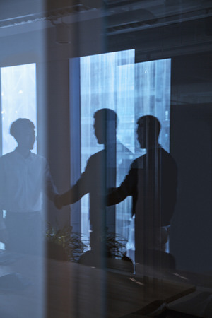 Reflection of two businessmen shaking hands photo