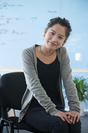 Young businesswoman in casual clothes sitting in the office, portrait  photo