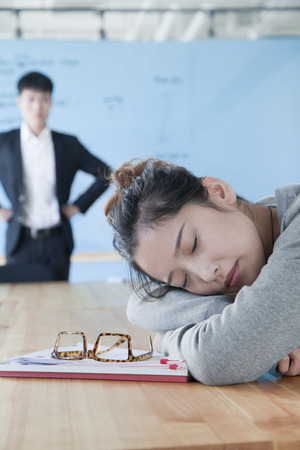 Young businesswoman sleeping during meeting, disappointed Boss looking at her  photo