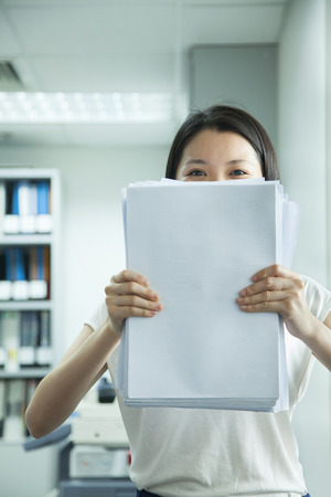 Businesswoman Hiding Behind Paper