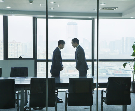 bowing: Two Businessmen Bowing to Each Other Stock Photo