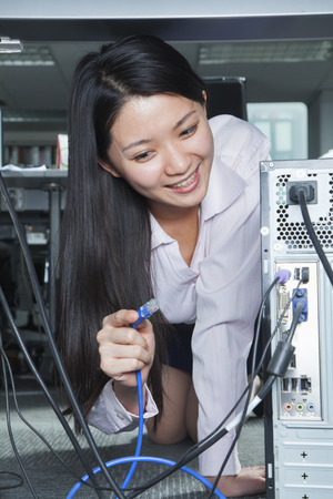 plugging: Businesswoman Plugging Cord Into Back of Computer