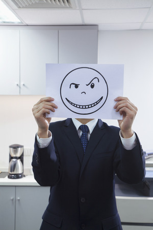Businessman Holding Happy Face on Paper Over Face photo