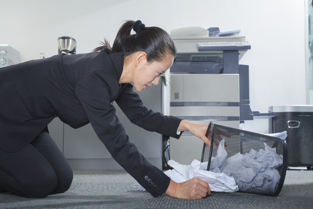 trashcan: Businesswoman Looking for Papers in Trashcan Stock Photo